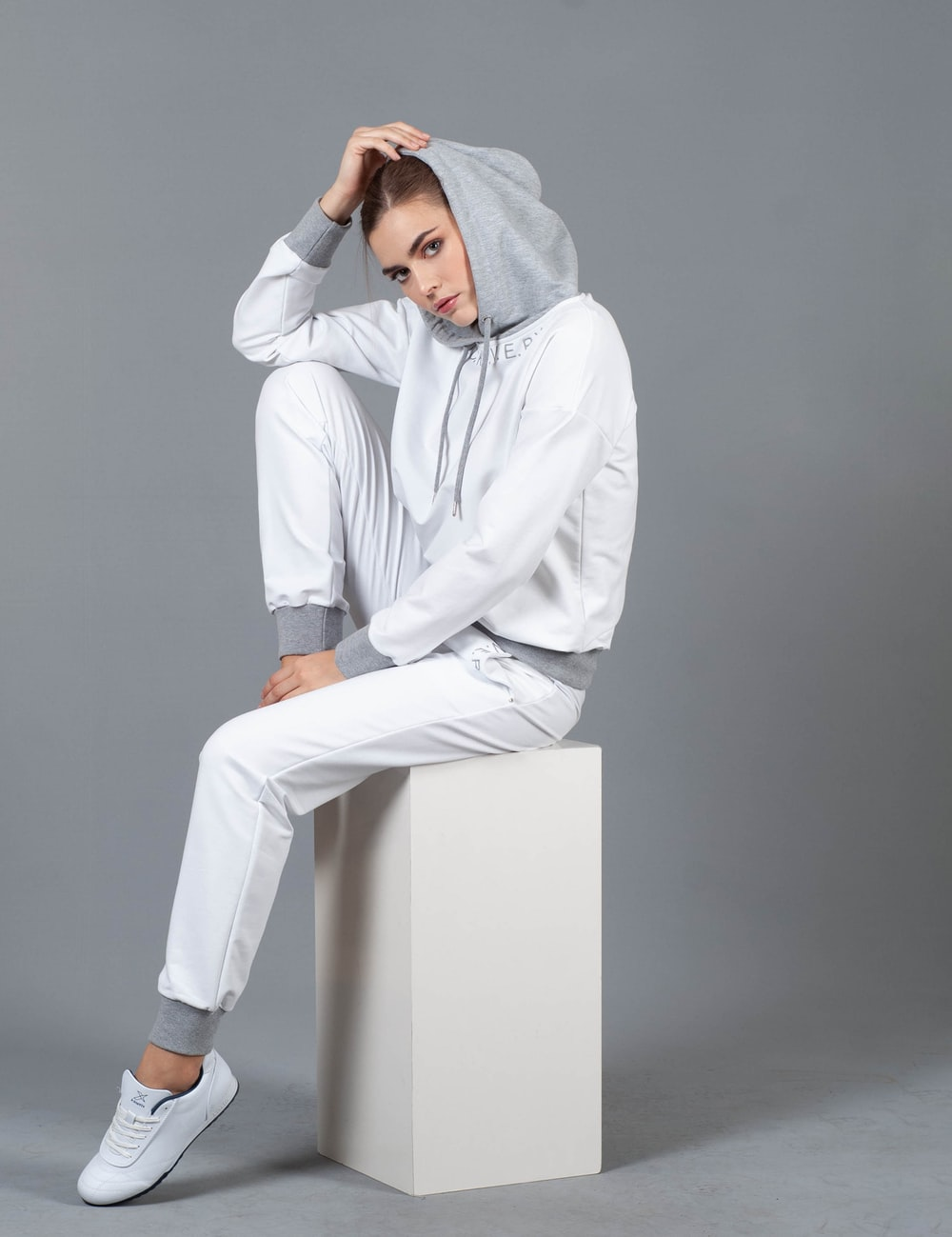 woman sitting on white box wearing hoodie holding her head