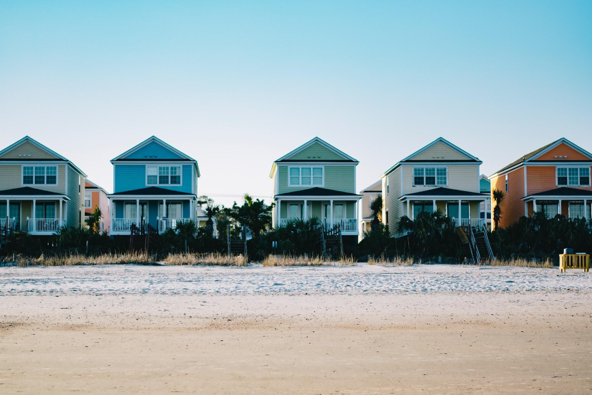 Na imagem cinco casas enfileiradas, cada casa de uma cor (bege, azul claro verde claro, pérola e alaranjado). Todas com varanda e localizadas a beira mar. A luz é de nascer do sol.