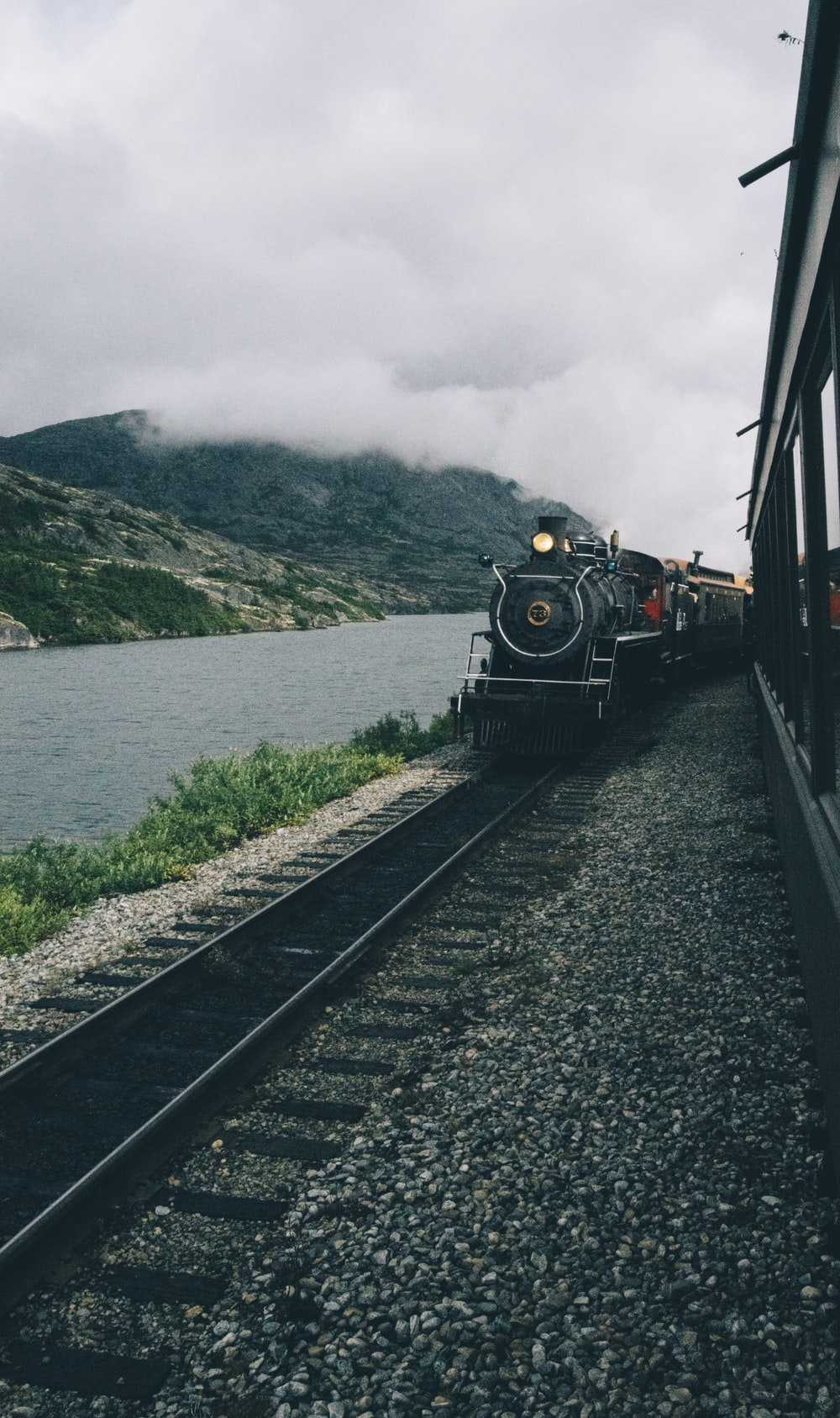 black train passing beside body of water under cloudy sky during daytime