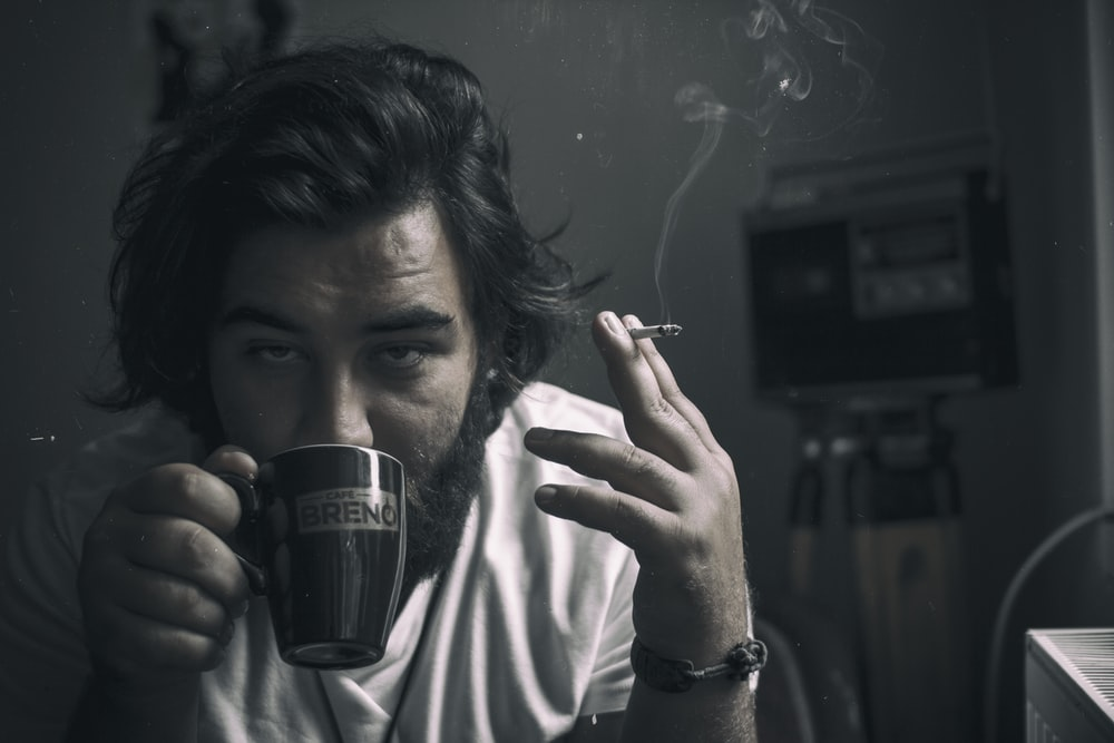man holding cigarette while drinking cup