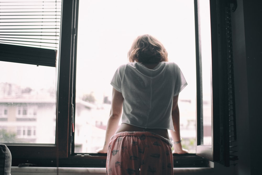 woman leaning on opened window at daytime