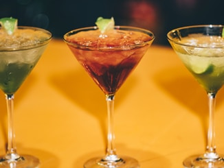 three assorted cocktails in martini glasses