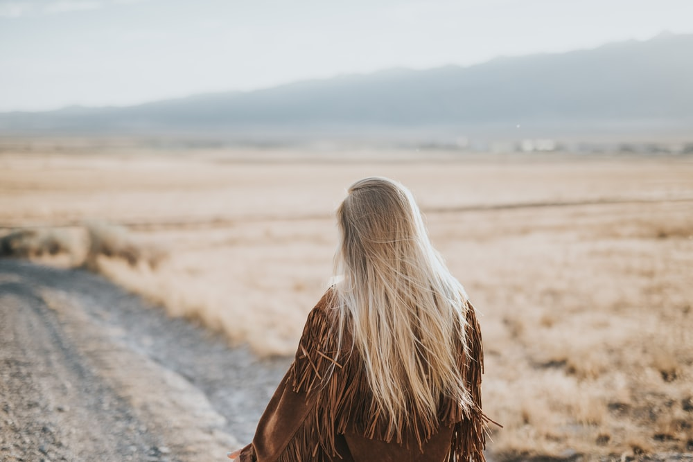 woman walking on gray sand