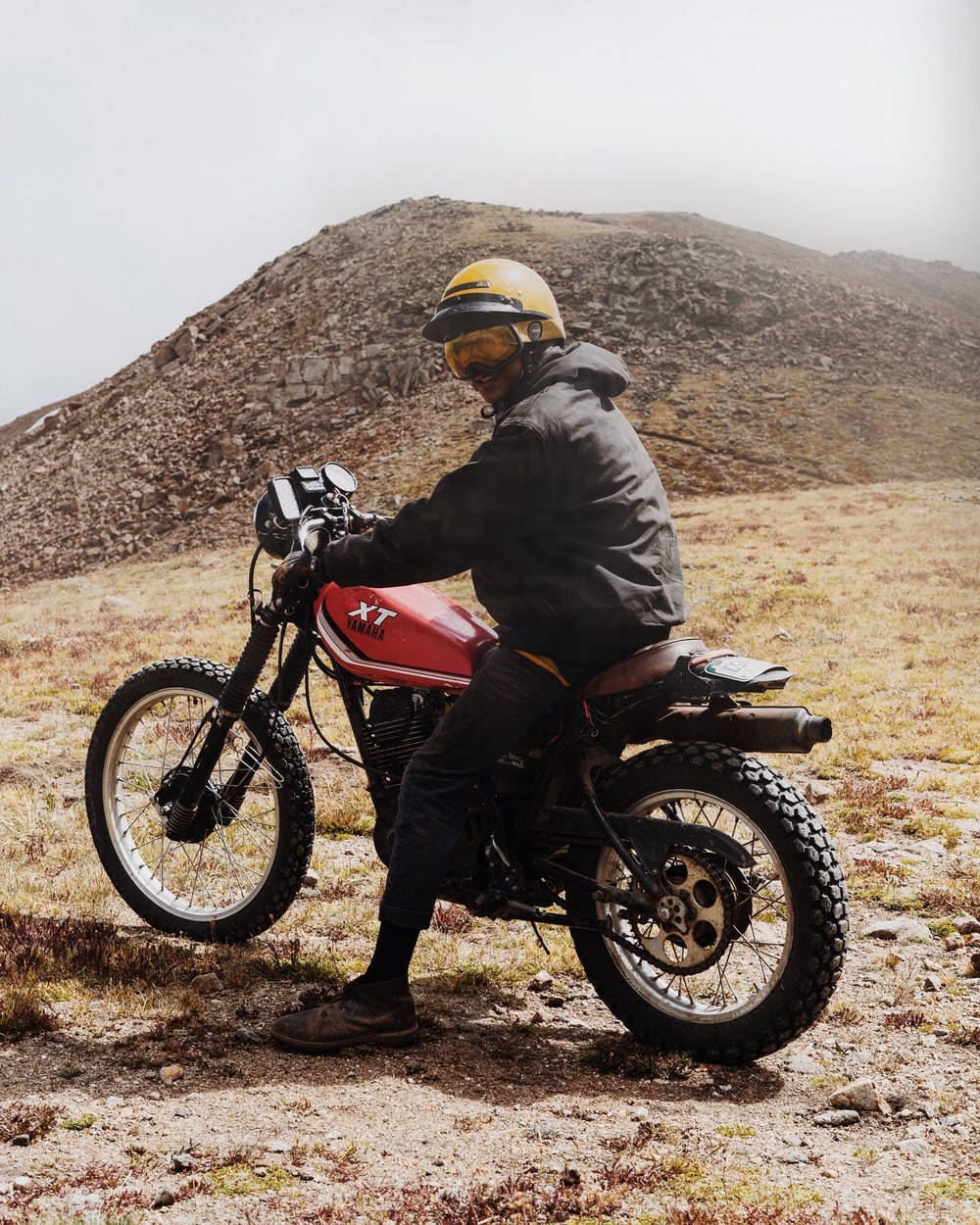 man in gray jacket riding dirt bike