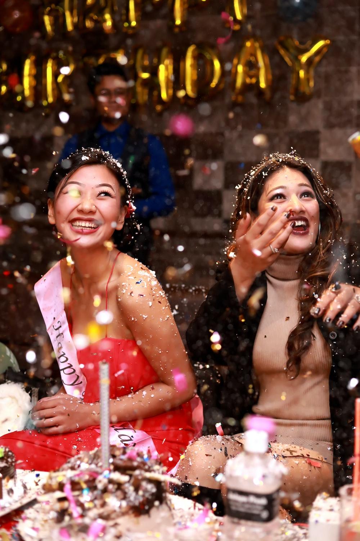 time-lapse photography of two women splashing glitters