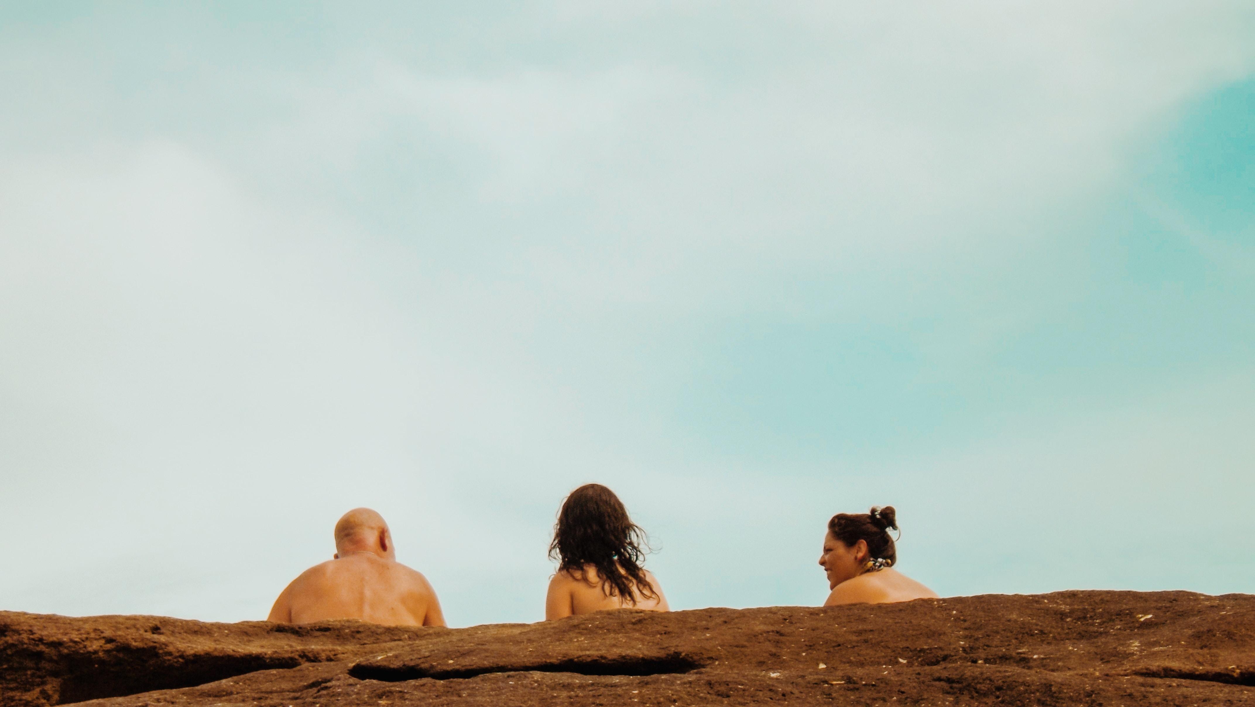 three people standing on brown soil
