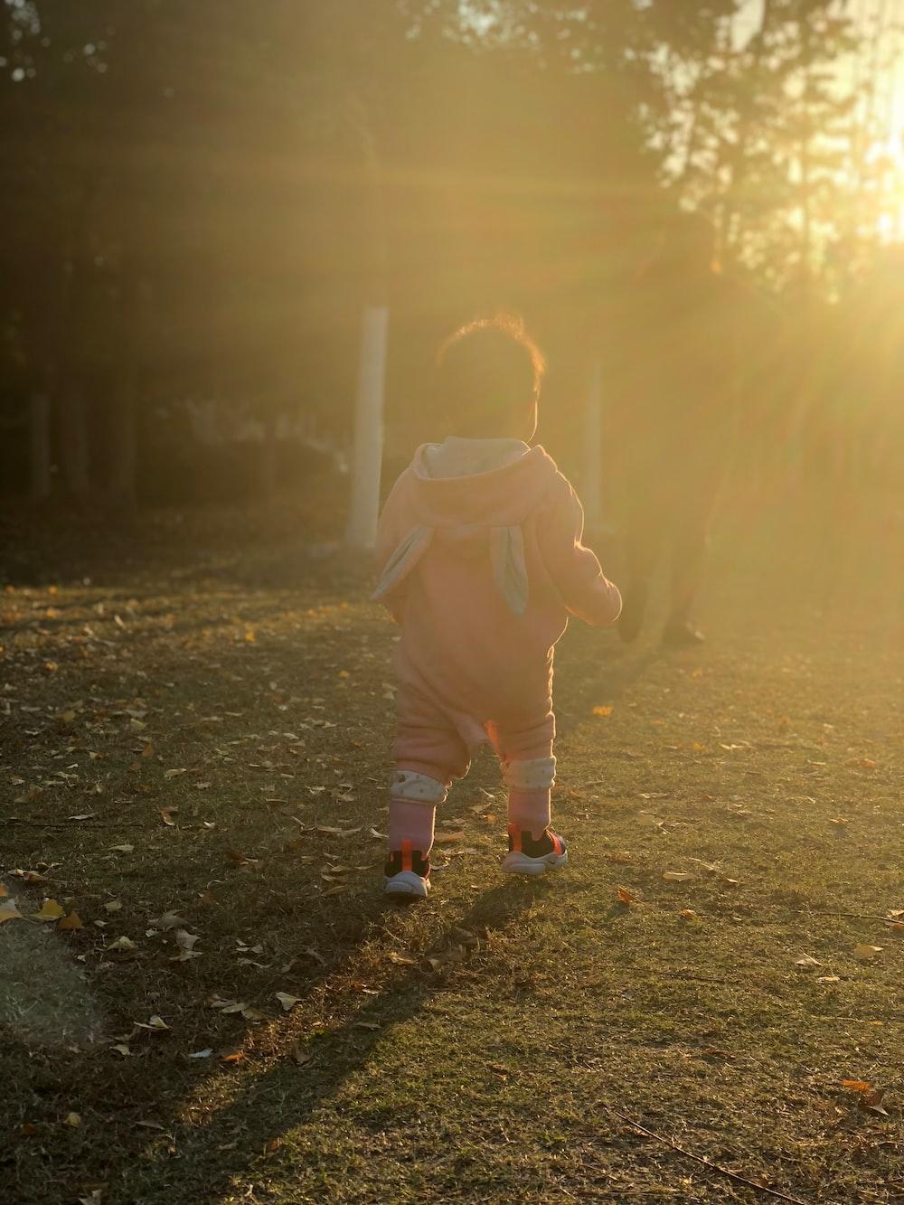toddler walking towards trees