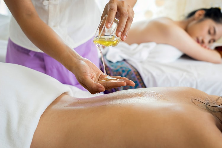 A massage therapist pours oil into their hand while two patients lie on massage tables.
