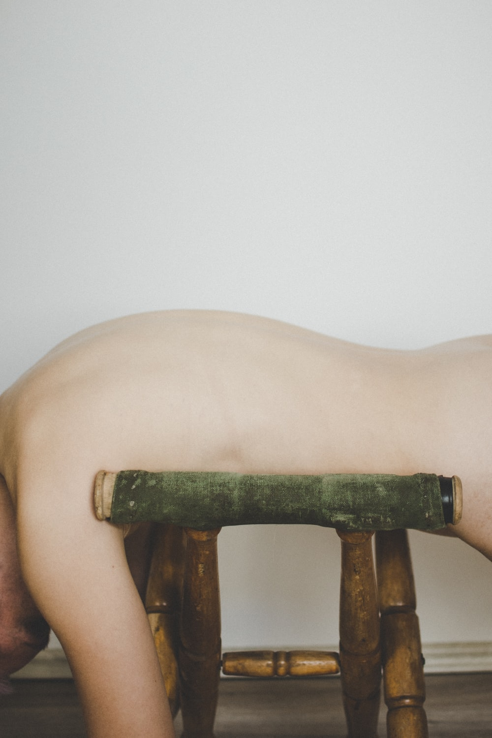 naked person on brown wooden bench