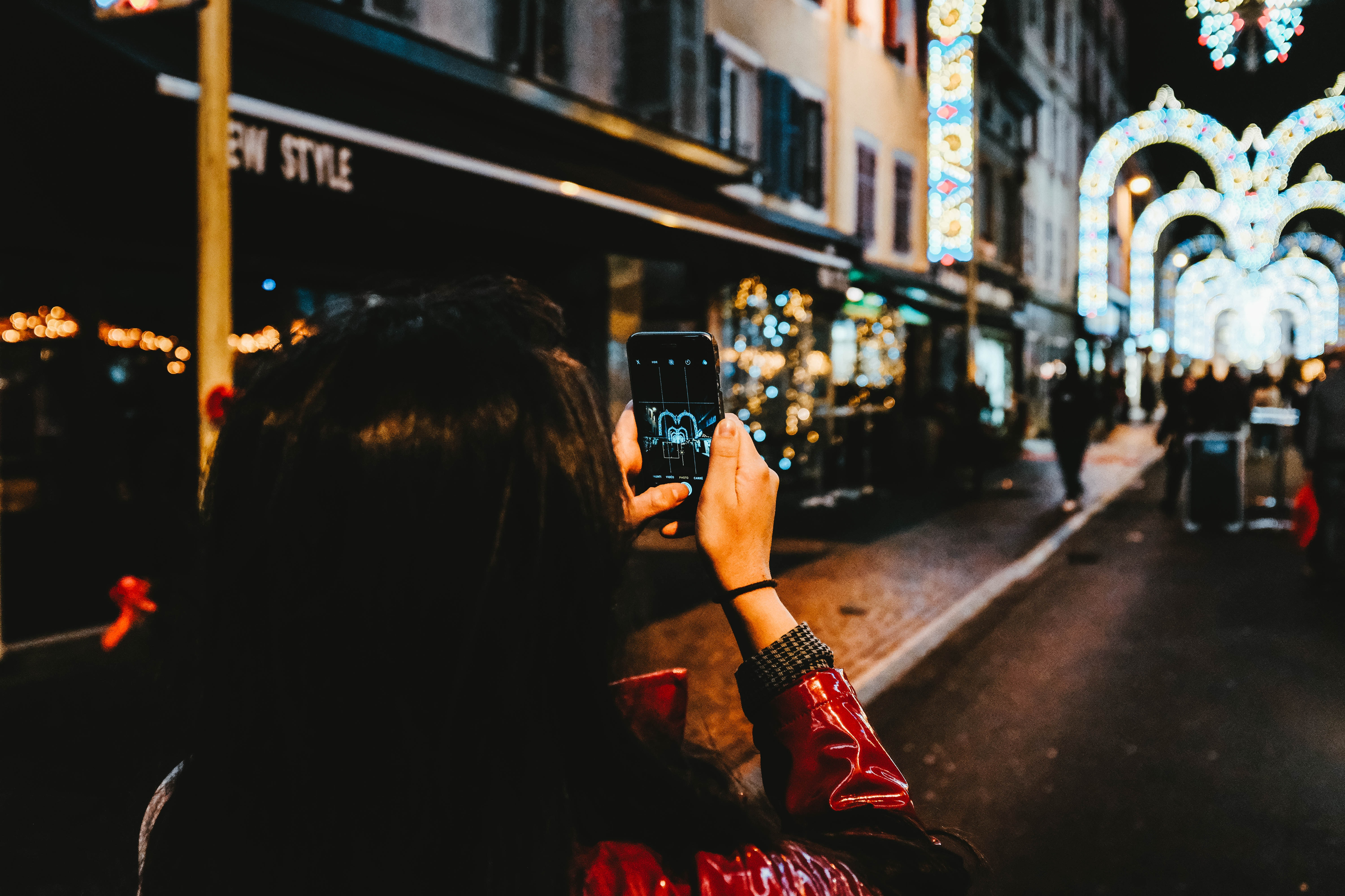 woman taking photo of arched street decors with string lights at night