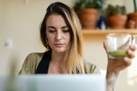 selective focus photography woman holding glass cup while using laptop inside well-lit room
