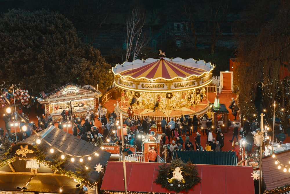 people standing near merry-go-round on amusement park during night time