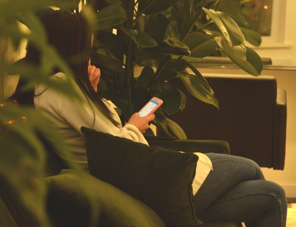 person using smartphone while sitting on black sofa between green plants