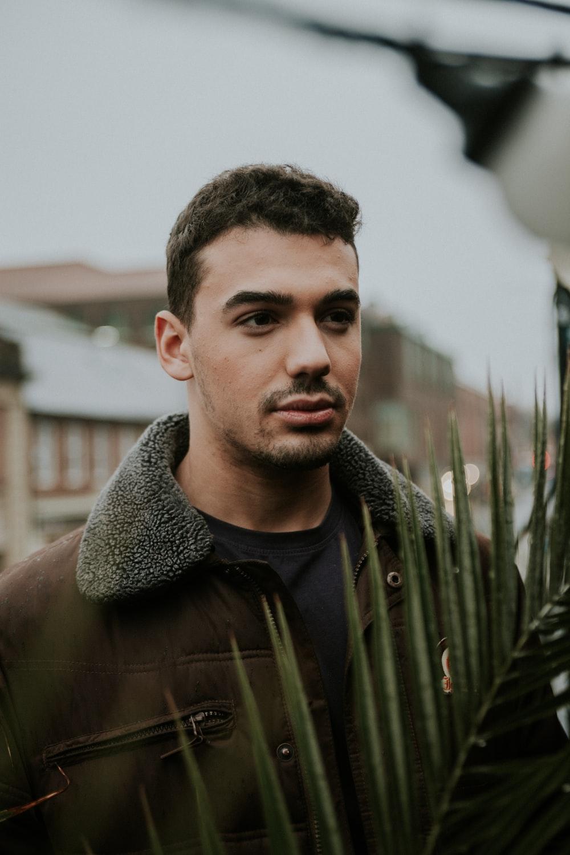man wearing jacket standing beside coconut plant