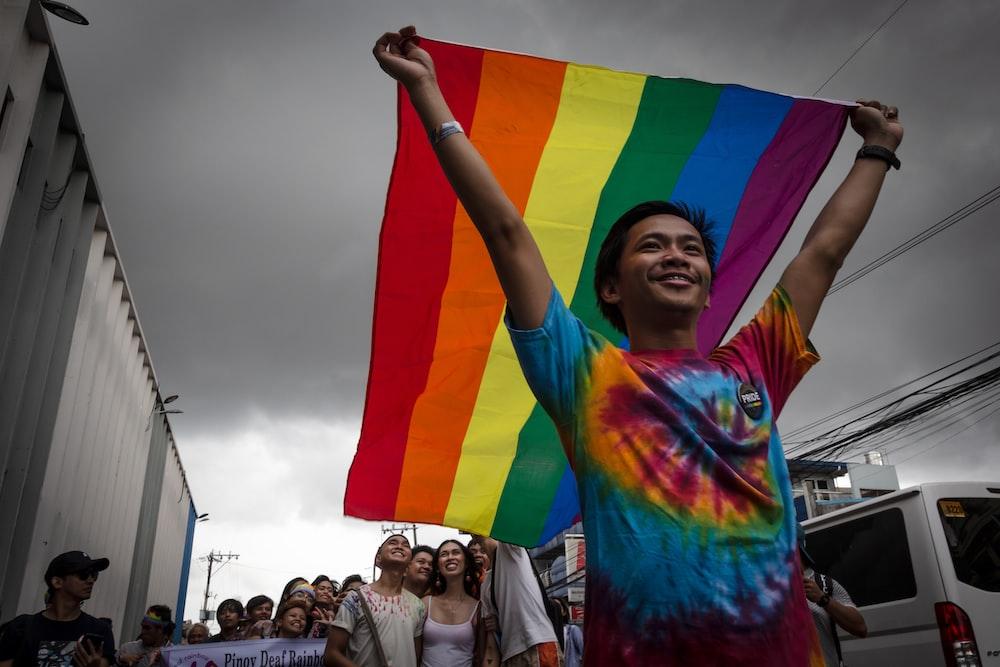 man holding LGBT flag