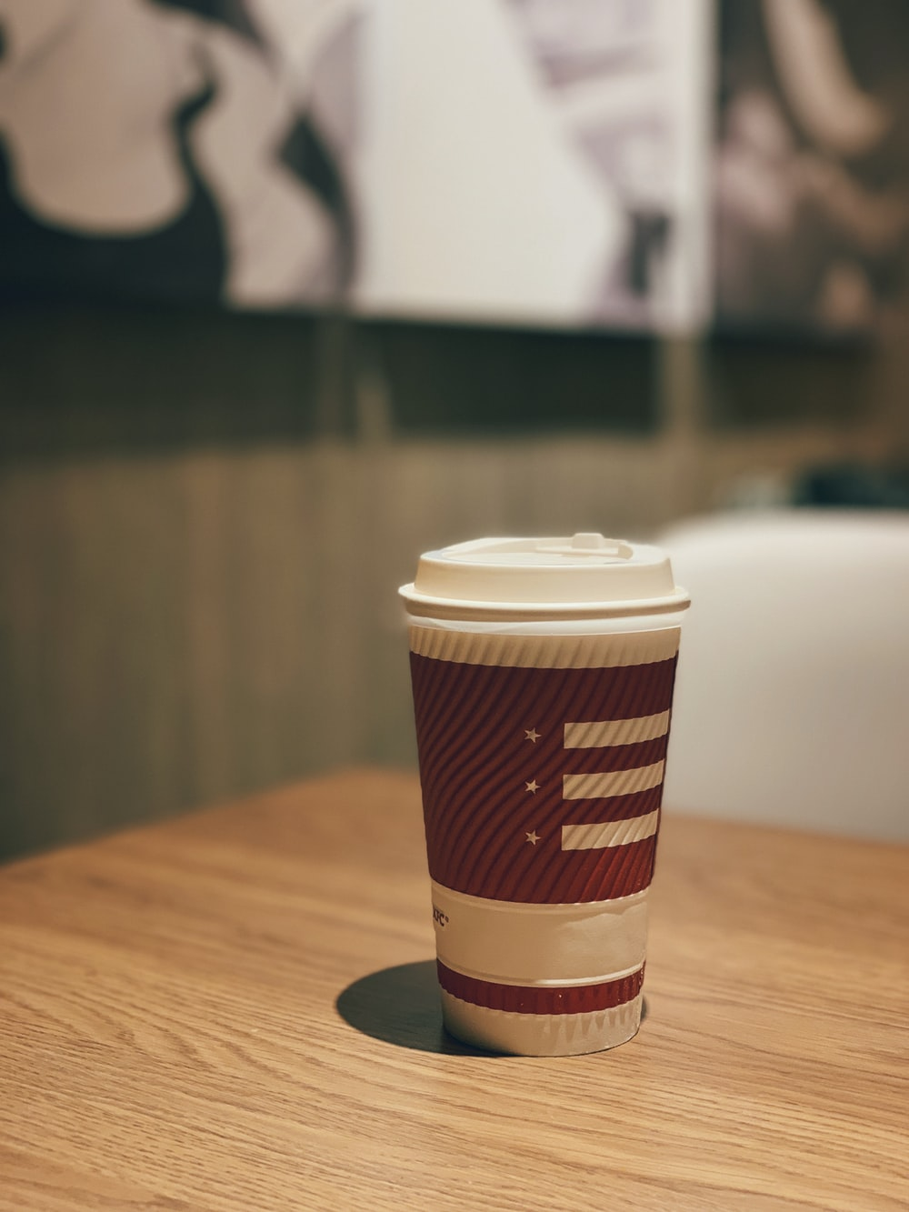 white and maroon disposable cup with lid on table