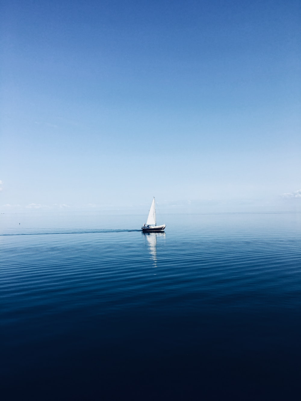 white sailboat at middle of ocean