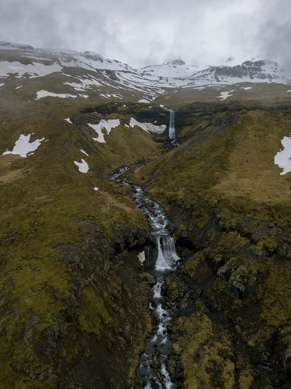 waterfall and river between hills