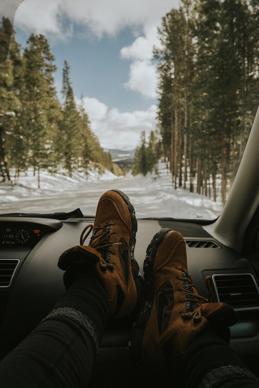 man resting his feet on vehicle dashboard