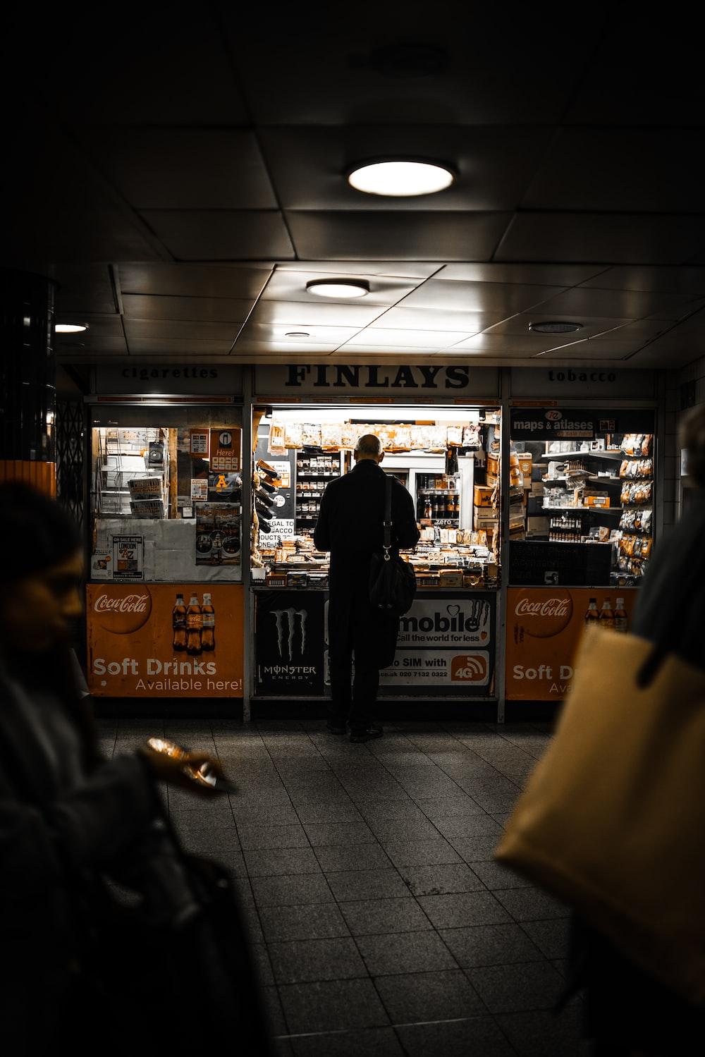 man standing beside food kart