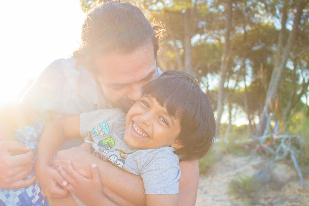 man kissing child during golden hour