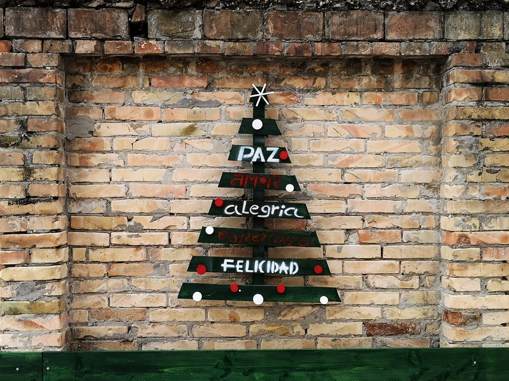 green, white, and red wooden Christmas tree mounted on brown wall