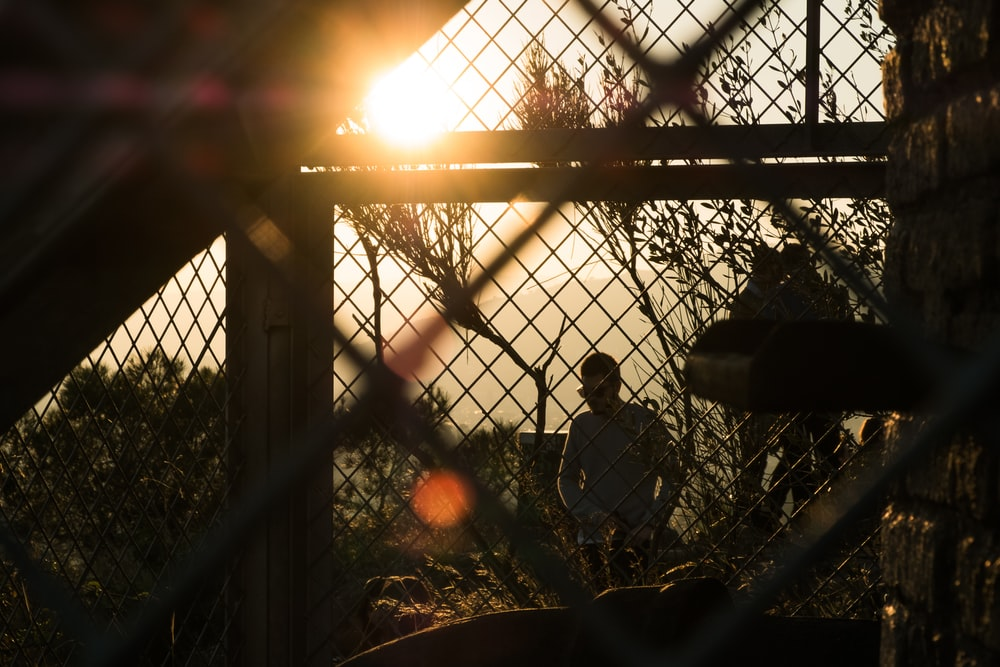 silhouette photography of man standing beside fence