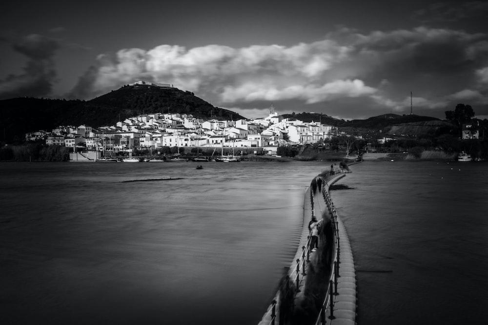 grayscale photography of beach docks near village and mountain range