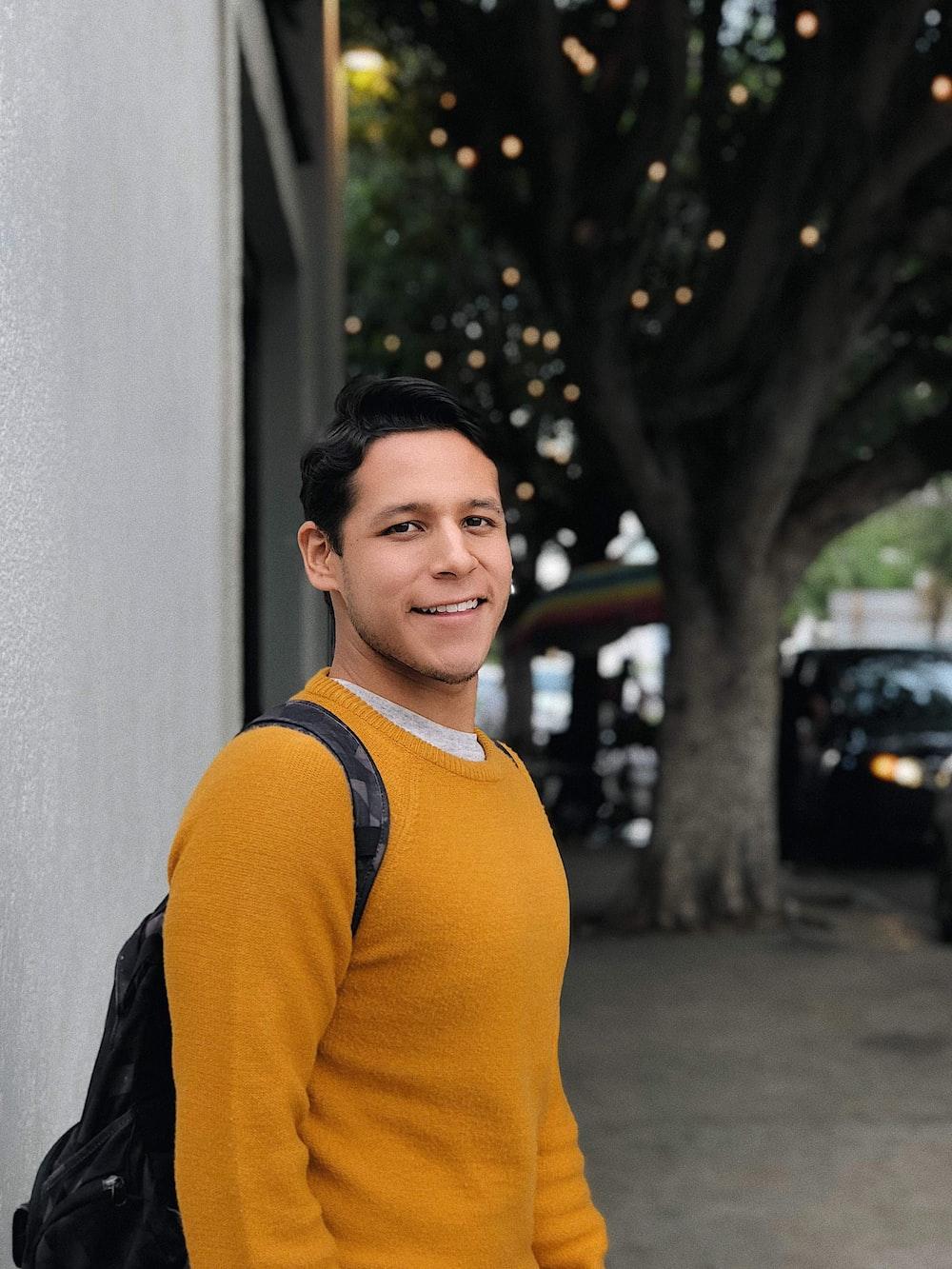 man wearing orange crew-neck sweater