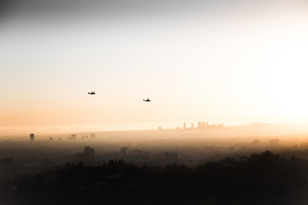 two helicopters flying over the city