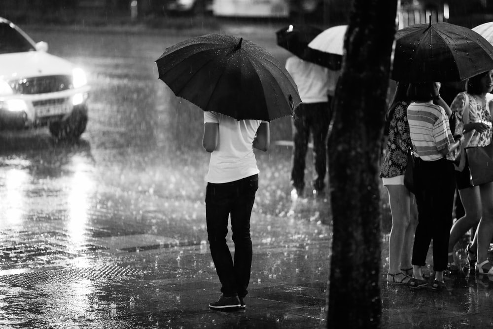 grayscale photography of people standing on road during rainy season