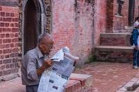 man reading newspaper sitting on concrete bench