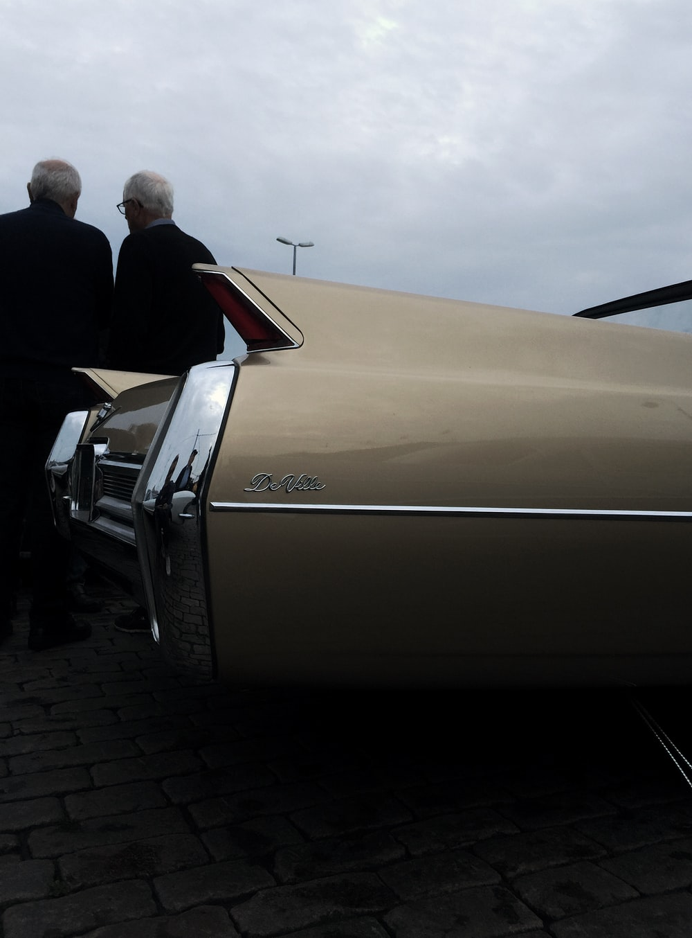 two men beside gold car