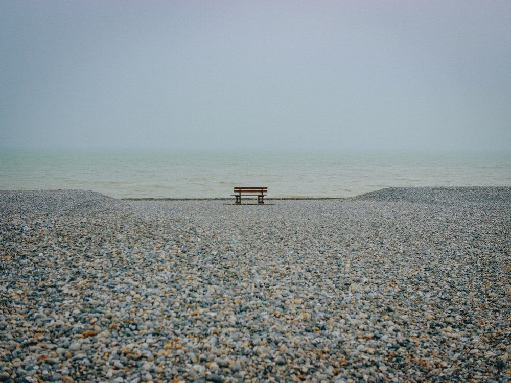brown bench on rock near water under white clouds