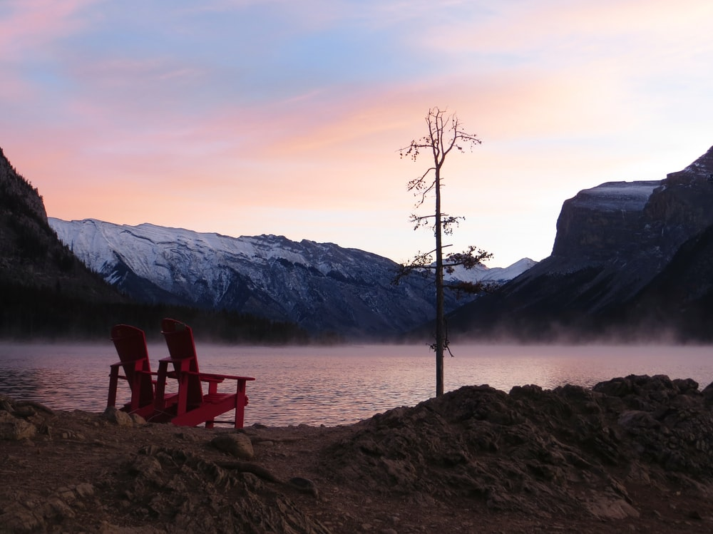two red wooden adirondack chairs beside water