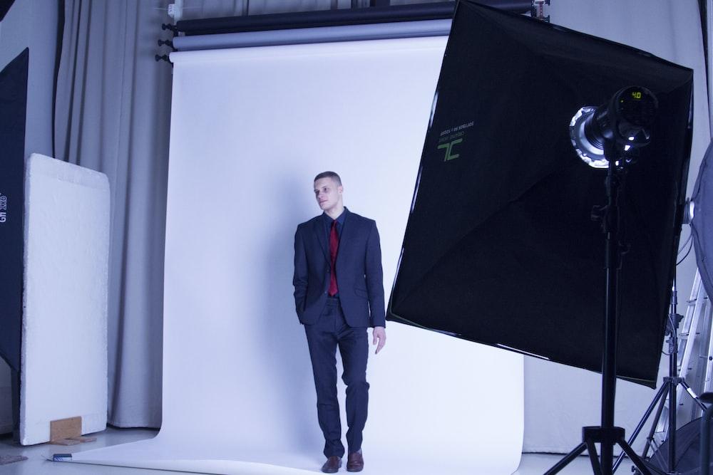 man in black suit standing beside canvas inside studio