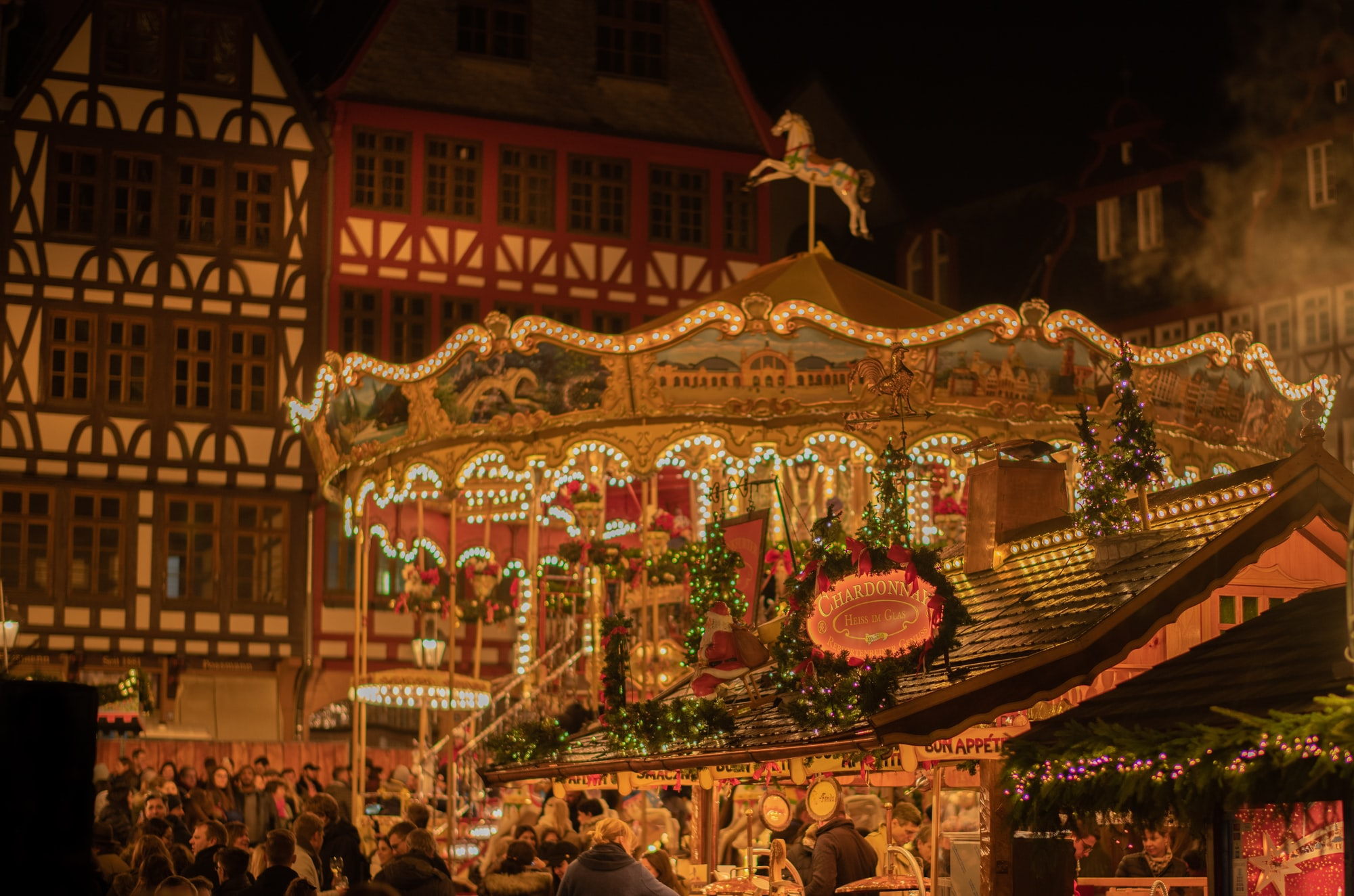 """a beautiful historic carousel at the Frankfurt Christmas Market in Germany. The amazing medieval truss houses create an unfathomable beautiful """"winter wonderland"""" atmosphere."""