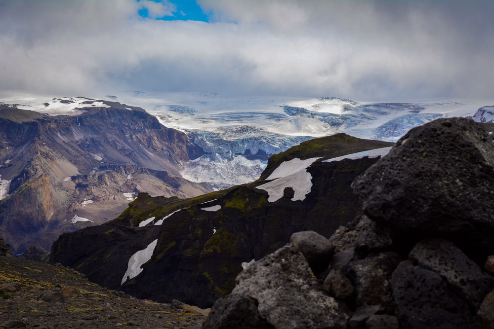 mountain range under dramatic clouds during daytime