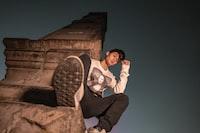 man sitting on brown concrete tower