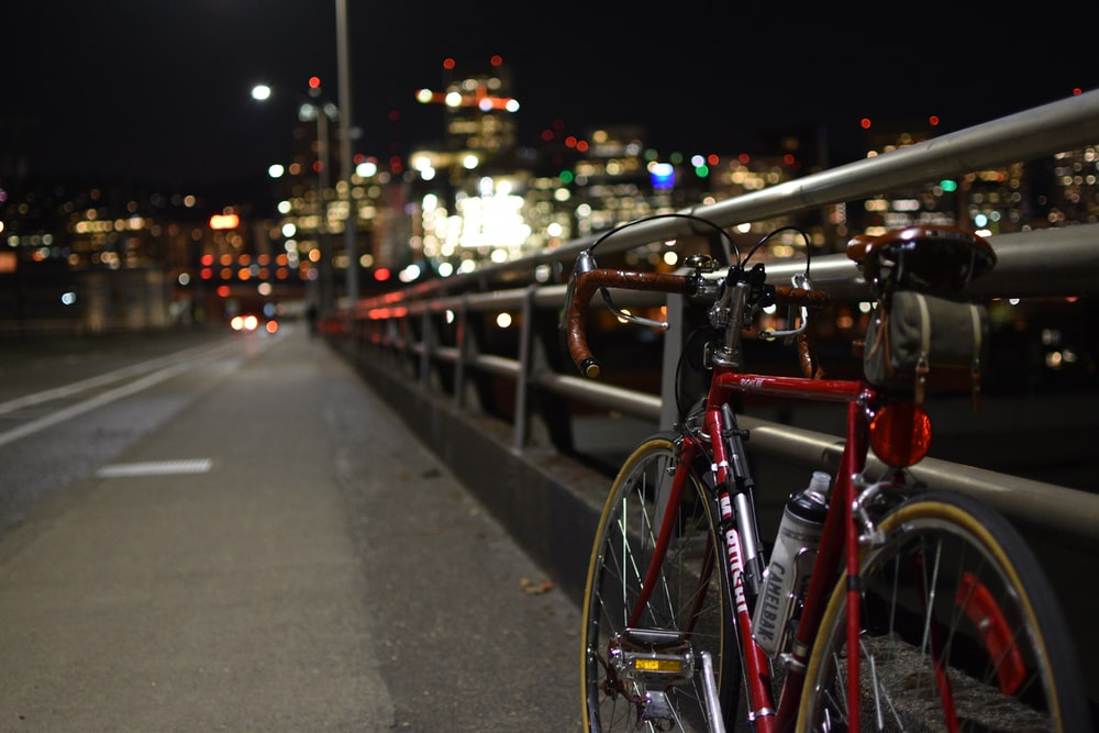 red road bike parked in rail