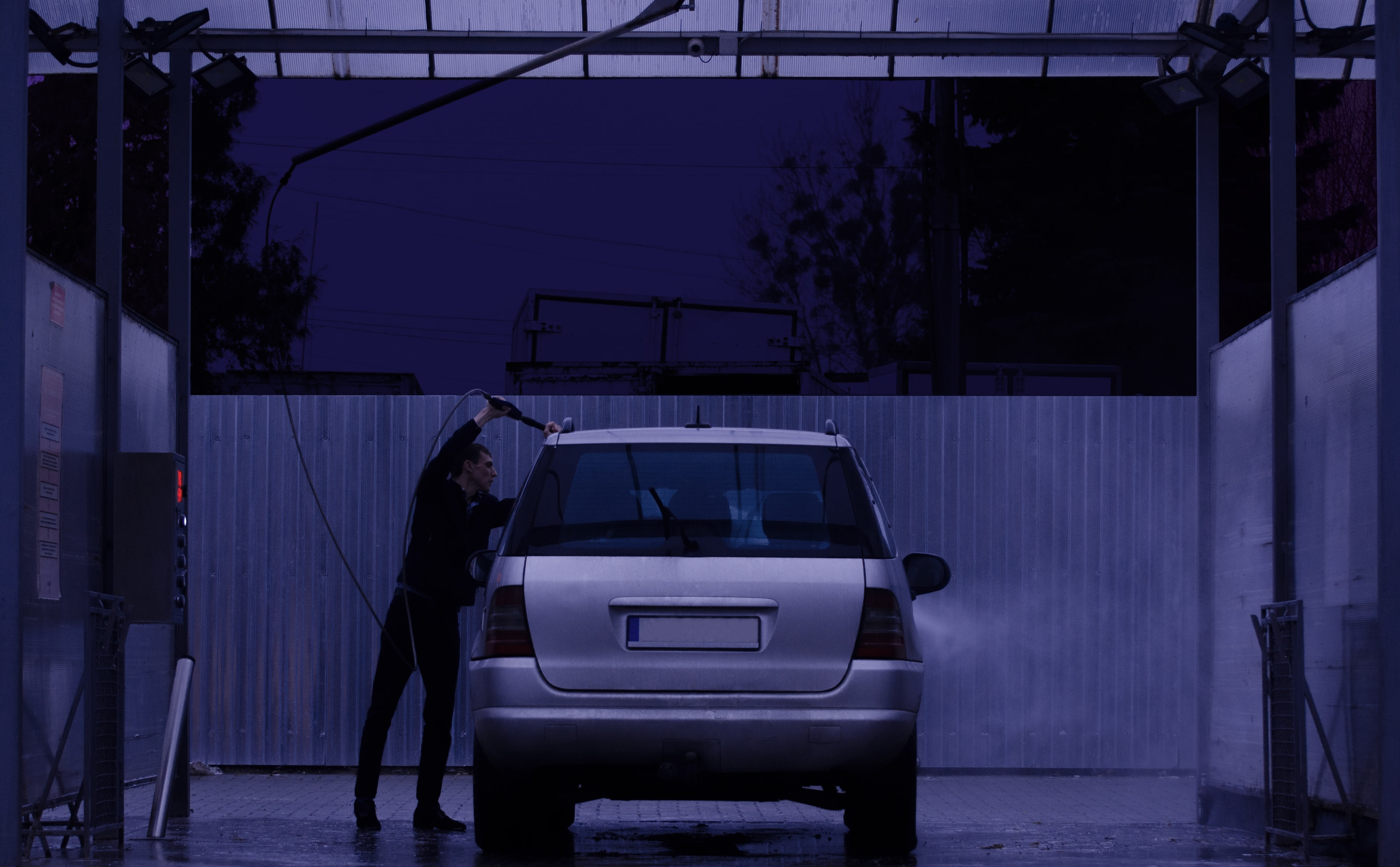 man cleaning gray vehicle