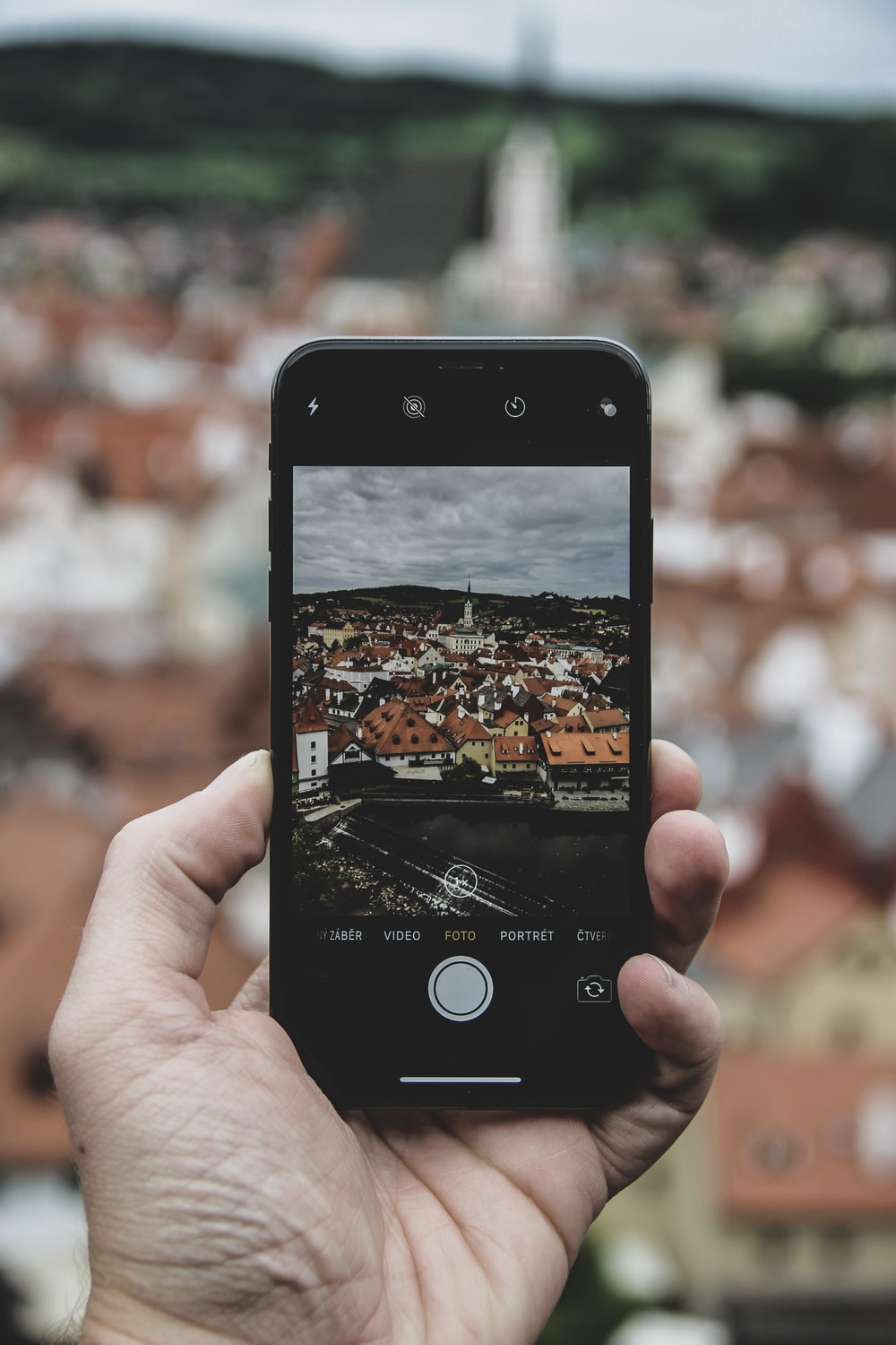 person holding iPhone while taking photo of cathedral