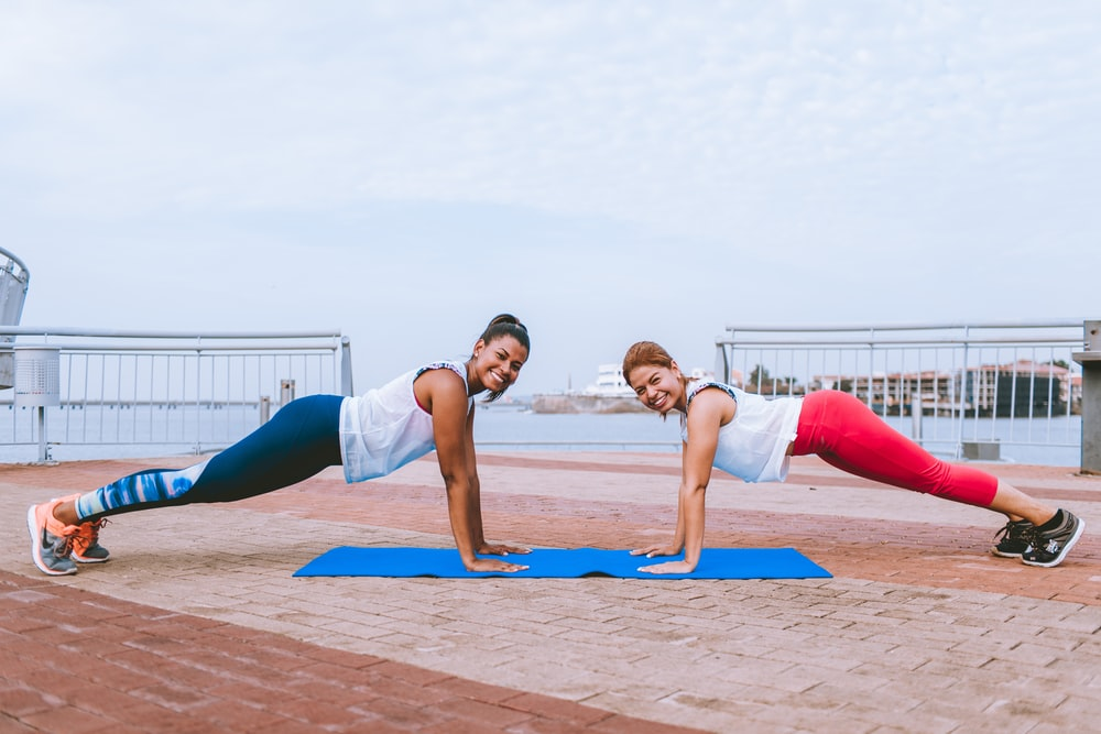smiling woman doing push up outdoor