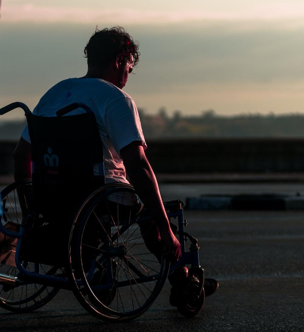 man riding on wheelchair during daytime