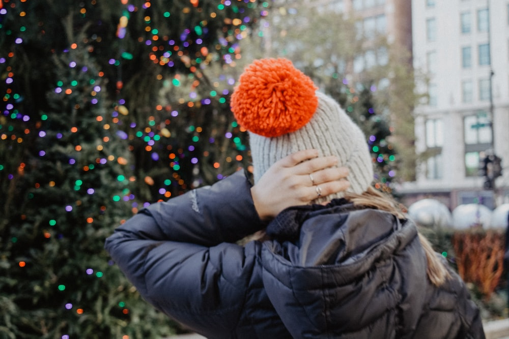 woman wearing black hoodie with knit cap near christmas tree