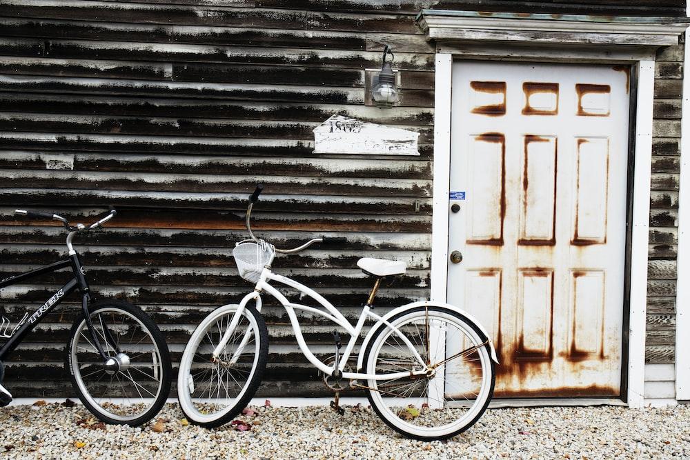 white cruiser bike parked beside white wooden door