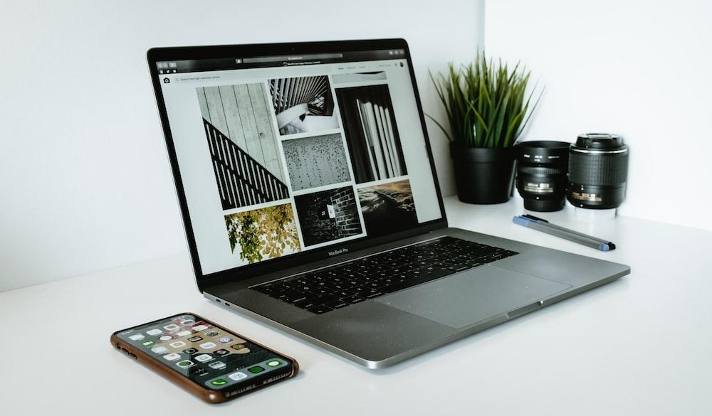 silver laptop computer beside black smartphon
