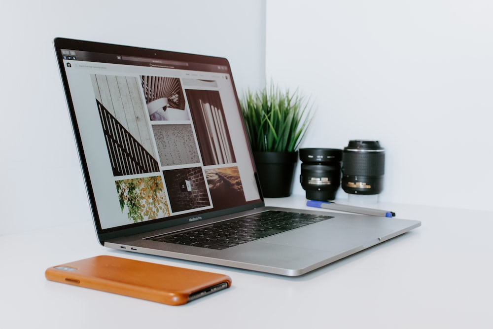 opened MacBook Air beside smartphone, potted plant, and camera lenses