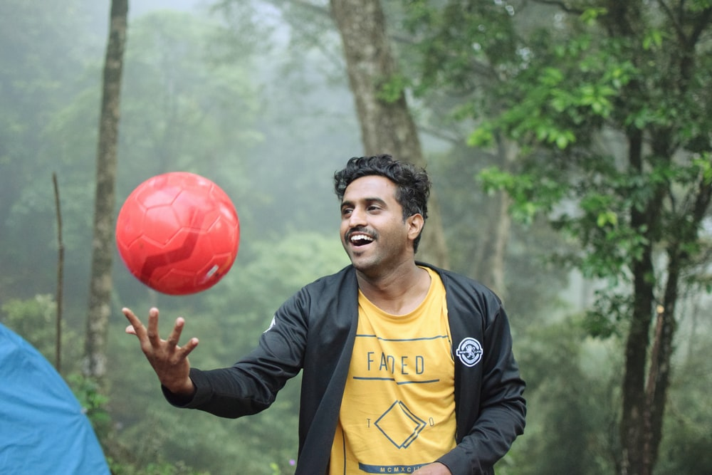 man playing red soccer ball