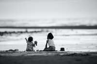 grayscale photography of two girls sitting on shore